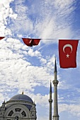 View of dome of mosque, minarets, clouds and Turkish flag