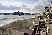 Türkei, Bodrum, Tische am Strand, Touristen