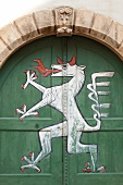 Close-up of archway and painting of dragon on green gate in Styria, Austria