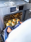 Small soufflés being removed from a steam oven