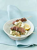 Lamb skewers date with quinoa tabouleh, cheese and lime on serving dish