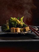 Broccoli with sesame dressing and fried tofu on plate