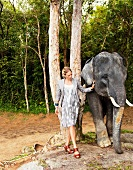 Pretty woman wearing gray dress standing next to elephant in jungle