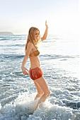 Frau im Bikini steht in der Brandung , bewegt sich, lächelt