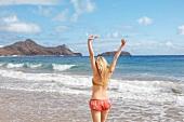 Rücken einer Frau, die vor dem Meer steht, Arme nach oben gestreckt