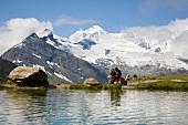 Wallis, Wanderer machen Rast am Ufer des Kreuzbodensee bei Saas-Grund