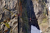 Tourist walking on tight rope while crossing valley