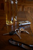 Car keys, cell phone and glasses on wooden table