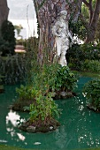 White statue of woman near pond in garden at Costa Brava, Spain