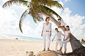 Family in white outfit standing under palm tree on beach in summer