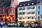 Guests sitting at table in front of Cathedral Square in Freiburg, Black Forest, Germany