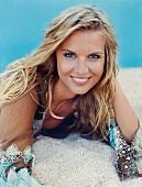 Blonde Frau in brauner Tunika liegt am Strand, lächelt in Kamera