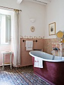 Bathroom with free-standing bathtub and cement mosaic tiles in Tuscan country house