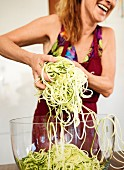 A woman preparing a vegetable spaghetti salad