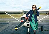 Frau steht im elegenten Outfit vor einer Propellermaschine