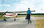 Frau steht auf einem Flugplatz neben einer Propellermaschine