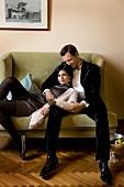 Paar in Abendgarderobe kuschelt auf einem Sofa