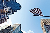 Low angle view of American flag waving on skyscrapers in New York, USA