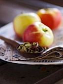 An arrangement of cardamom pods, star anise and apples in the background