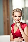 Frau blond, Ohrringe, Kleid rot, festlich, lacht, Kamerablick