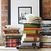 Bücherstapel auf Ablage vor Backsteinwand