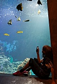 Girl sitting beside and taking photographs of tropical aquarium, Bremerhaven, Germany
