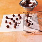 Schokolade, in Kuvertüre getauchte Trüffel auf Gitter ablegen