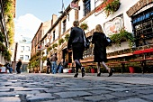 Low angle view of people walking through Cathedral Quarter pubs, Belfast, Ireland