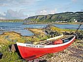 Red boat on rocky coast of Rathlin Island in Ireland