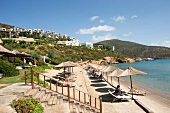 People relaxing in sun shade on beach near Kempinski Hotel Barbaros Bay Bodrum, Turkey