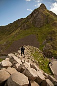 Man walking on Giant's Causeway overlooking mountain at Antrim coast, Ireland