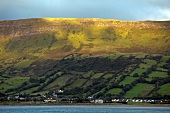 View of green pastures and village at Antrim coast, Ireland, UK