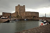 Boats moored at harbour in front of Carrickfergus Castle, Carrickfergus, Ireland