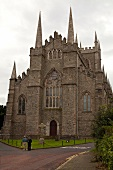 People standing in front of facade of Clonard Monastery in Belfast, Ireland