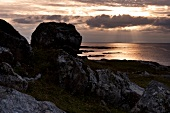 View of rocky coast overlooking sea at sunset in Fanad, Ireland