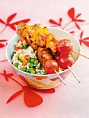 Pork skewers with peppers and tomatoes on a bed of vegetable rice
