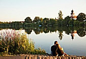 Couples sitting at shore overlooking church in Neckarhausen, Germany
