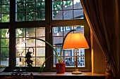 Illuminated lamp and potted plant at the window pane
