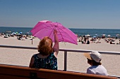 Woman sitting with child and opening umbrella at Long Beach Island, New York, USA
