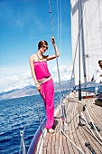 Glamorous woman wearing pink outfit and sunglasses standing on deck of sailing ship