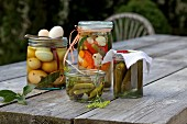 Preserved vegetables and pickled eggs in jars on a table outside