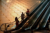 People on escalator in an office building in New York, USA