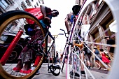 Low angle view of two people standing with bicycles on Broadway in Soho, New York, USA