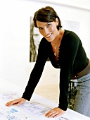 Portrait of mosaic artist Nicole Zach leaning on table, smiling