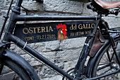 Close-up of bicycle with advertising sign, Como, Lombardy, Italy