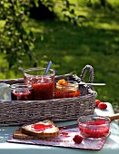 Various jars of homemade jam on a tray on a table outside