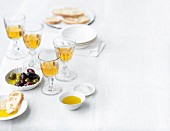 Glasses of sweet wine served with olives, white bread and olive oil on a table