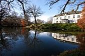 Ostseeküste: Blick auf Herrenhaus Gelting, Fassade weiss, Wasser