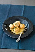 Potato dumplings with almonds and saffron served with lemon sauce