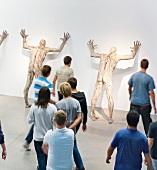 Visitors looking at human figures at Zagreb museum, Croatia